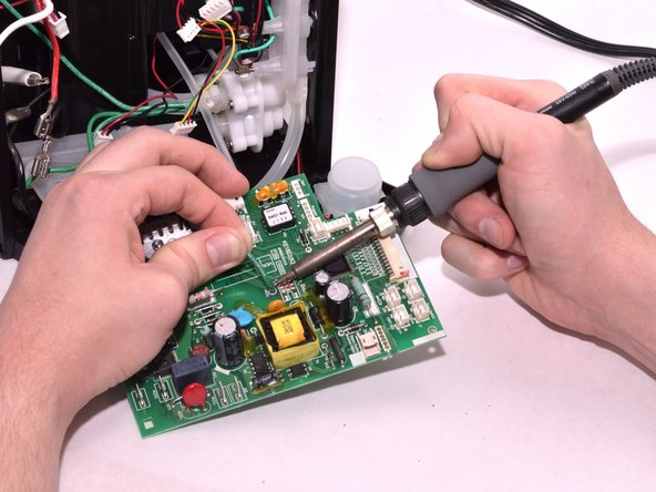In order to free the circuit board completely, you have to desolder the connections that restrain it. Use our How to Solder and Desolder Connections Guide to properly and safely conduct this procedure.