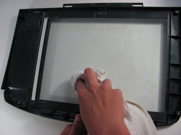 Moisten a lint-free cloth with alcohol. Wipe down the underside of the scanner glass until all dust is removed.