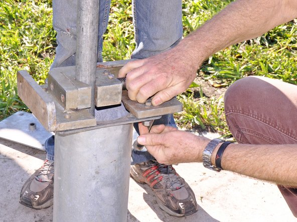 Secure the base clamp to the pump base with two bolt and nut sets installed on opposite sides of each other.