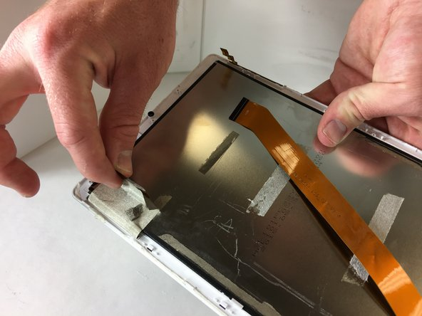 Peel away the grey mesh tape that holds down the touch digitizer's  ribbon cable to the front case.