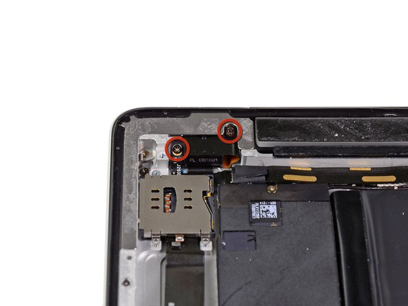 Remove the two 2.9 mm Phillips screws securing the headphone jack to the top edge of the rear panel.