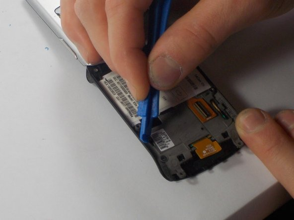 Using a plastic opening tool, push the four metal tabs along the edge of the phone in towards the keypad.