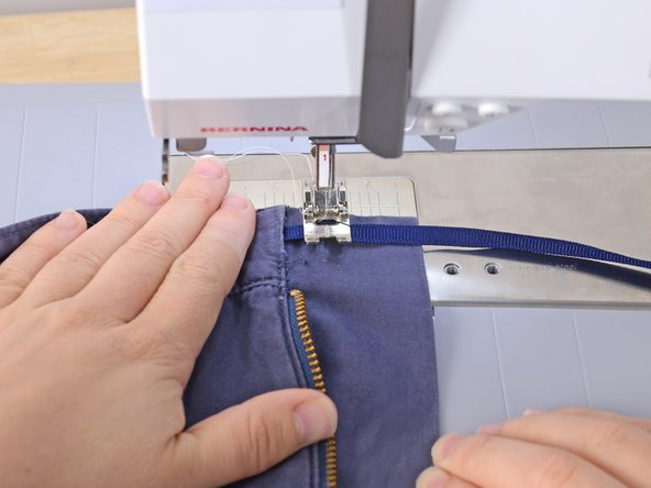 Holding the ribbon in place, slide the garment into the sewing machine, aligning the presser foot with the place you want the button to sit.