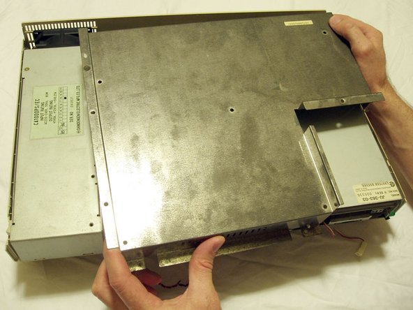 Gently remove the metal shield to reveal the system board, floppy disk drive and power supply.