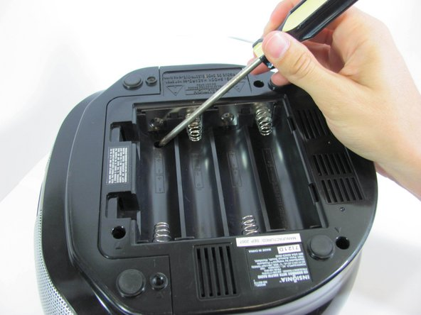 Using a long Phillips #2 screwdriver, remove one 6mm screw located inside the battery compartment.