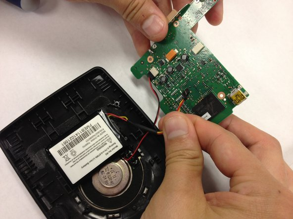 Plug the new battery into the white receptacle on the green motherboard.
