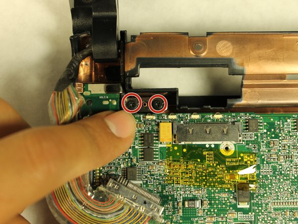Locate and remove the last two remaining 4.7mm screws in the upper left corner of the motherboard.