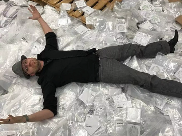 Eric Lundgren lays on a stack of Dell restore discs