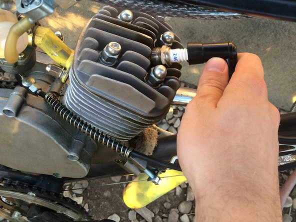 Detach the rubber CDI from the spark plug by gently pulling up and away from the engine.