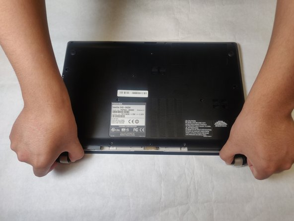 Lift up in the spaces left by the battery to create a gap between the back case and the laptop body.