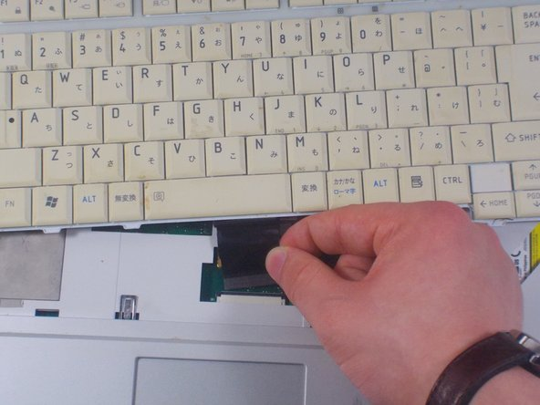 Pop out the black plastic tab on either side of the ribbon cable.  Holding the cable on each side,  detach from laptop.