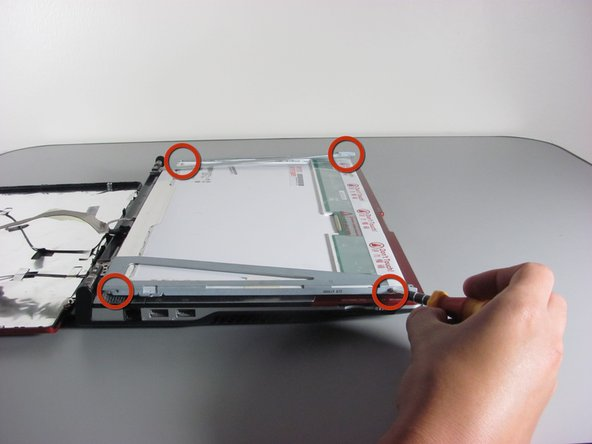 Remove the four 2.8 mm Phillips screws that secure the screen to the mounting bracket using a screwdriver.