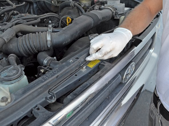 Image 1/2: Make sure the hood prop rod is secured in its holder to prevent damage.