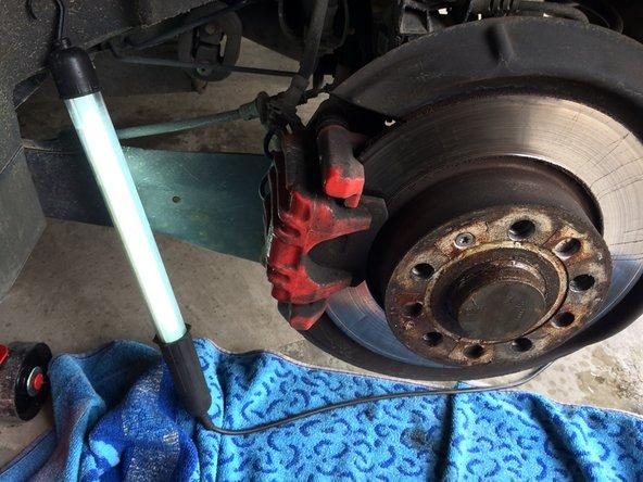 Wagen hinten aufbocken und Hinterrad abnehmen. Bremssattelschrauben lösen. Handbremsseil aushängen und nach hinten vollständig entfernen.