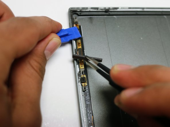 Make sure that you hold the left side of the tablet open with a plastic opening tool so that you will be able to take out the volume button.