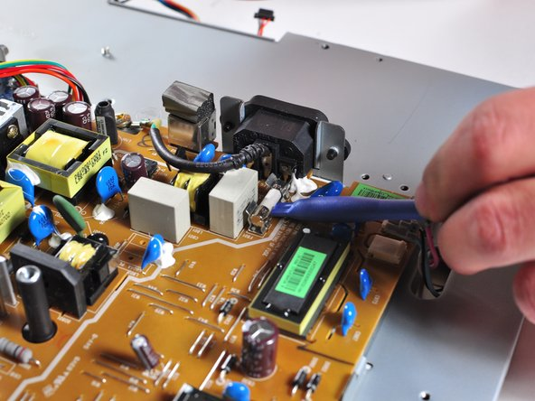 Carefully insert the prying tool underneath the power supply fuse.