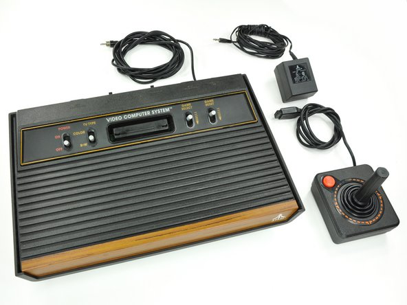 Atari 2600, with AC adapter and iconic joystick controller.