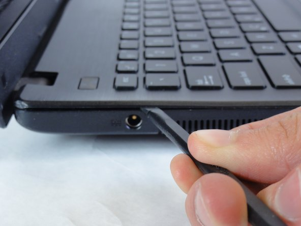 Insert the flat edge of the spudger into the crease of the keyboard cover.