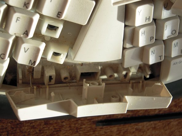 Use the flat end of a spudger to pop the keys off the keyboard.