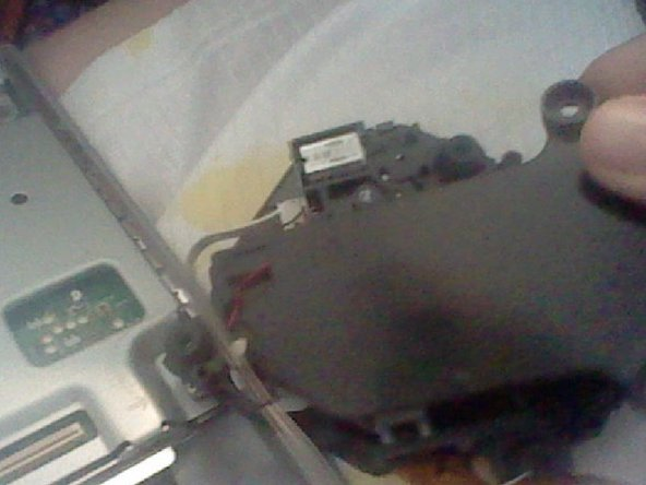 Take the bottom piece and screw the two screws on the new Optical Drive.