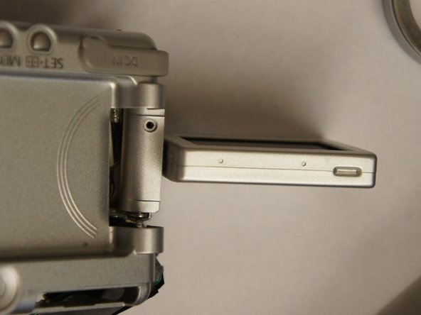 Twist the LCD screen so it is perpendicular to the camera and snap the back casing off.