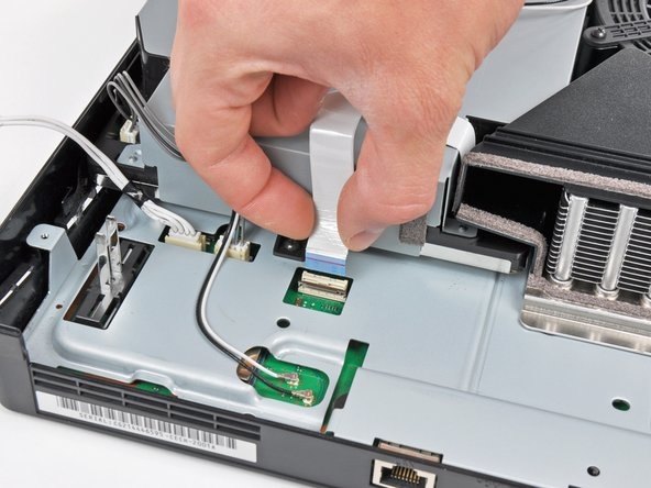 Image 1/1: Pull the Blu-ray ribbon cable straight up and out of its socket.