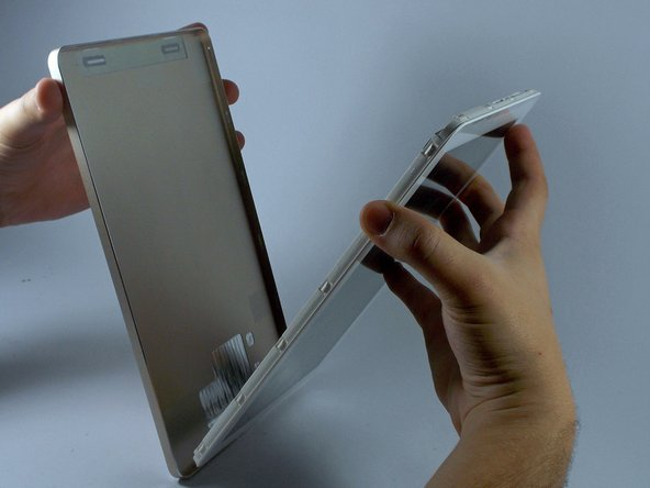 Using your hands and the separating tool, remove the back cover from the device.