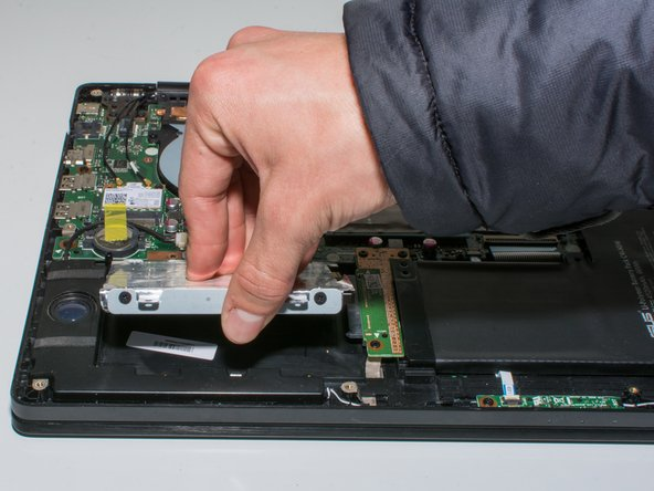 Once the hard drive has been removed from the connector, use your thumb to get under and lift the hard drive out.