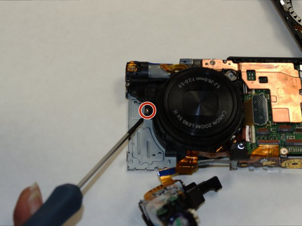 Remove the Phillips screw on the front facing side of the lens.