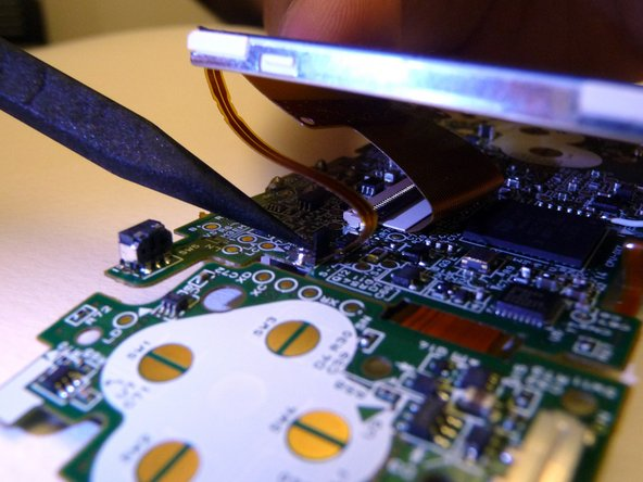 Image 1/3: With both tabs lifted, pull the ribbons off the motherboard and remove the LCD screen.