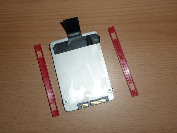 Remove the plastic rails from the old SSD/hard drive and place them on the new SSD/hard drive.