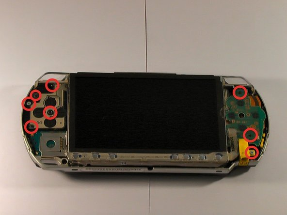 Image 2/3: Contrary to what this picture might suggest, this PSP hasn't contracted chickenpox. Each red circle indicates a screw that you need to remove.