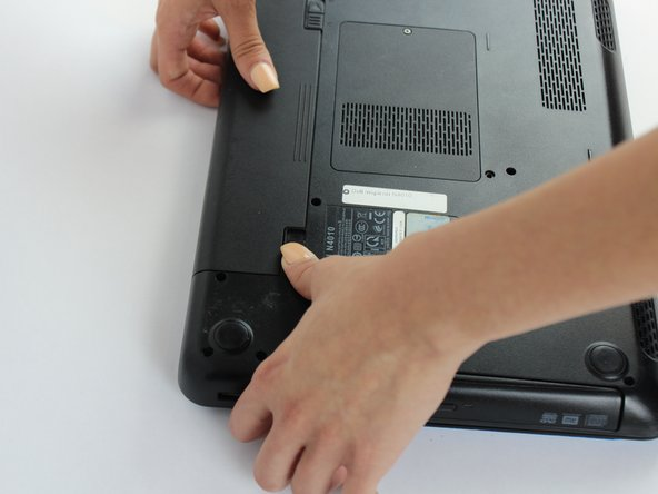While holding the left-hand switch to the left position, pull the battery away from the laptop.