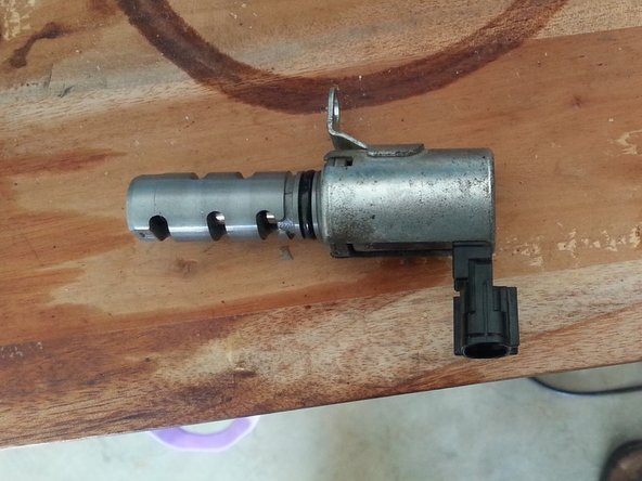 The bolt is located under the solenoid out of view. Use a size 10 socket to undo the bolt. Then remove the solenoid. You may need to use some force or multi grips to remove the solenoid.