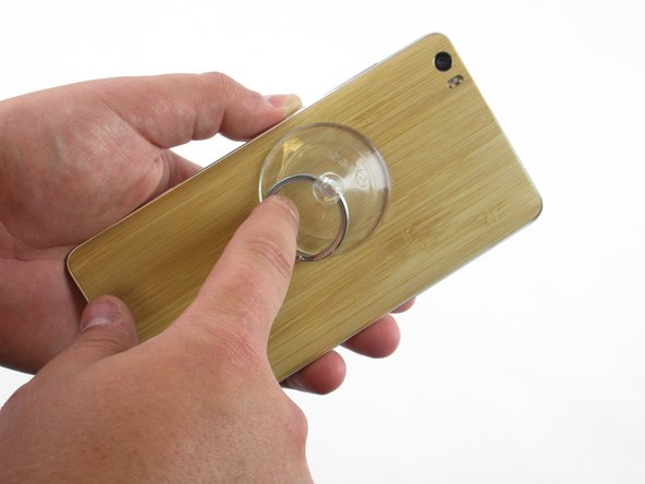 Use your suction cup to grip the back of the phone. Once the suction cup is secure, pull back with moderate force and the back plate should snap free.