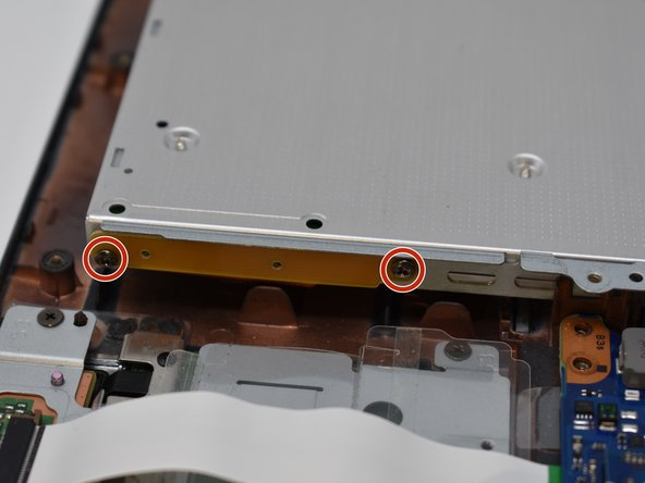 Remove two 2.5 mm screws from the side of the optical drive using a Phillips #0 screwdriver.