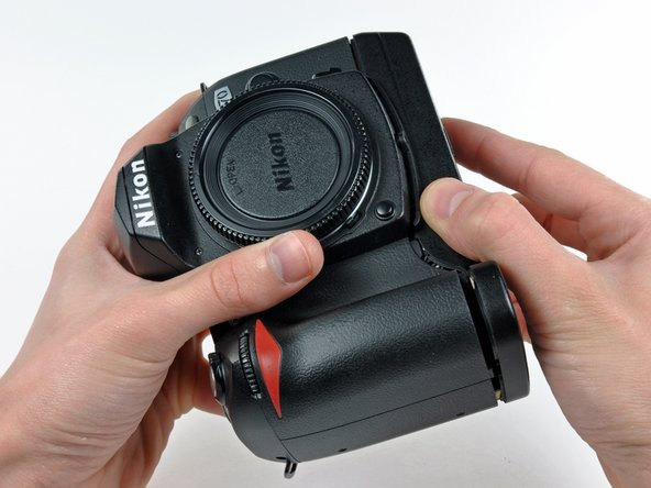 Image 1/2: Carefully pull the bottom cover to separate it from the body of the D70.