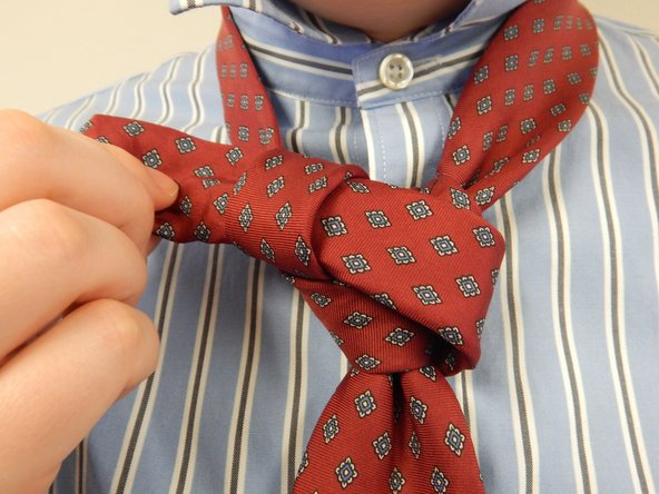 Tighten the neck knot by holding the knot and pulling on the narrow end of the tie away from you.