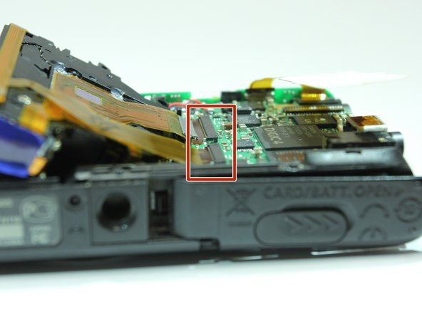 Image 1/3: Lift up the two black flaps on the motherboard that hold the electrical ribbons in place.
