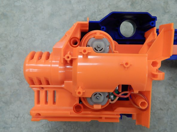 With your gun disassembled, locate the motor around the front portion of your gun as shown in Figure 1. Remove the two 9.0 mm Phillips screws securing the top shell of the motor casing.