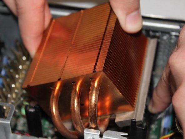 Slide the CPU heat sink from under the clip and pull upward.