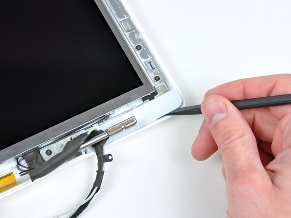 Image 1/2: Lift the right bezel cover off the display assembly.
