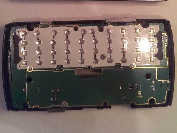 The keyboard is latched in about 6 places and can peeled away slowly and carefully. It is not held down with adhesive.
