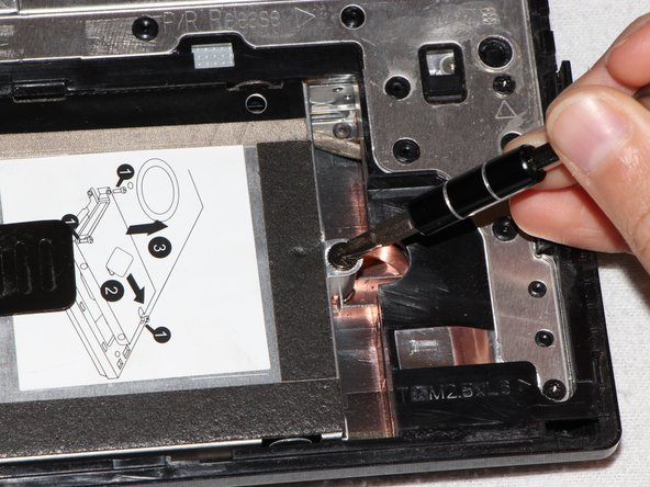 Image 2/3: Fully loosen the captive screw on the right using a Phillips (PH1) head screwdriver.