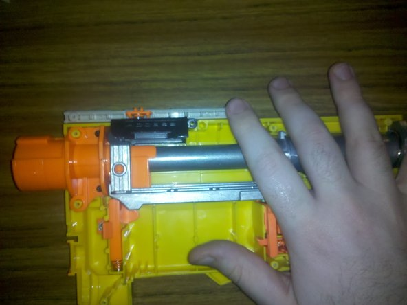 Holding your hand down over the sensitive internals around the trigger area (to prevent them from dislodging), slide the cocking mechanism all the way forward.