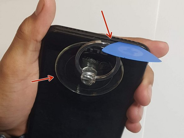 After removing the screws, begin by use the suction tool and pry tool, to slowly remove the black plate.