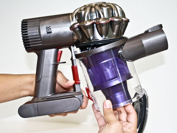 Push the red lever downward again while pulling the clear bin away from the main body of the Dyson vacuum.