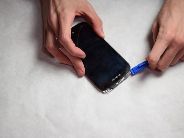 Separate the screen from the phone assembly by using a plastic opening tool.