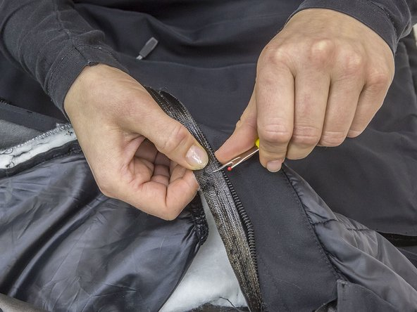 After you've separated the zip and front flap from the jacket, you'll need to separate the zip from the front flap. You should then have both sides of the zip and the front flap laying before you.