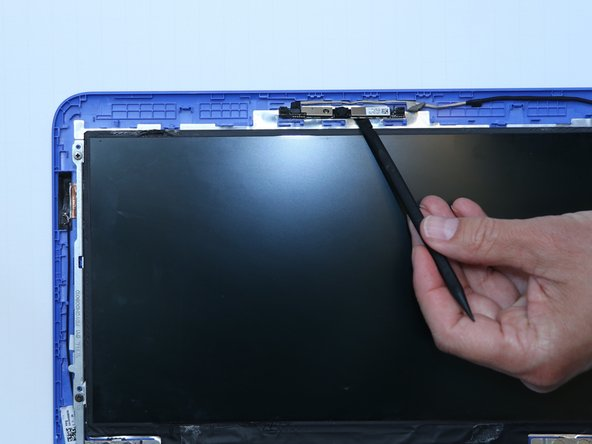 Use steady pressure with a plastic spudger to break the glue seal and release the webcam.